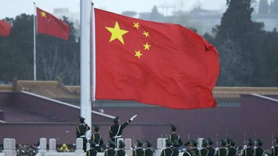 In this March 5, 2016, file photo, a Chinese flag is seen as paramilitary policemen perform a  ceremony on Tiananmen Square in Beijing.