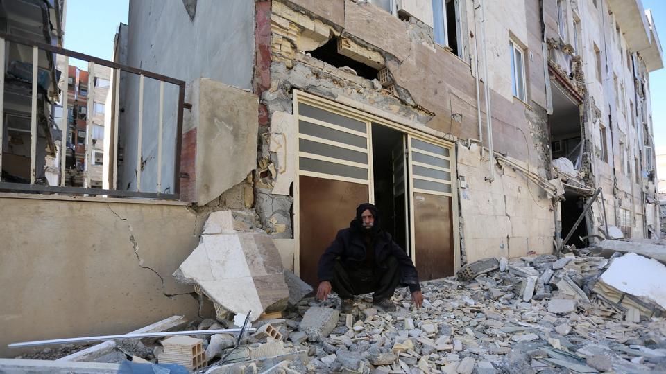 A man sits outside a damaged following a devastating 7.3-magnitude earthquake in Sarpol-e Zahab county in Kermanshah, Iran.