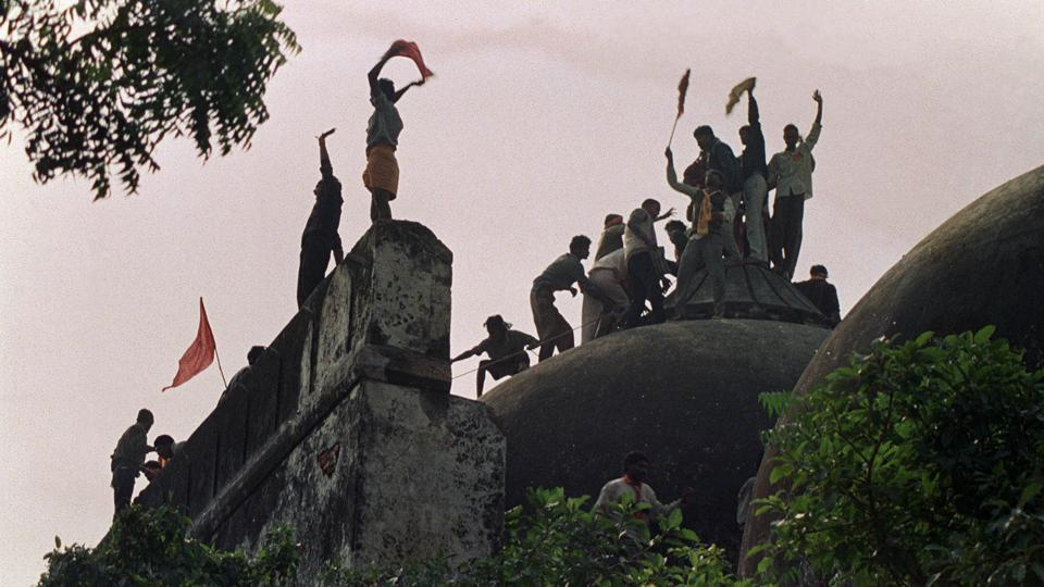 (FILES) This file photo taken on December 6, 1992 shows Hindu fundamentalists shouting and waving banners as they stand on the top of a stone wall and celebrate the destruction of the 16th Century Babri Mosque in Ayodhya.