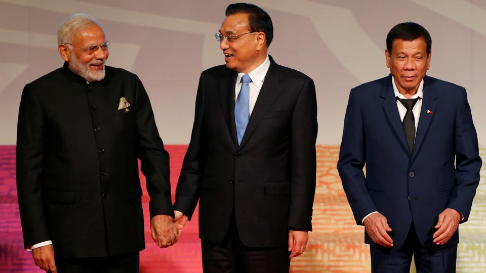 Prime Minister Narendra Modi (L) and Chinese Premier Li Keqiang hold hands as Philippine President Rodrigo Duterte prepares to walk to chair his meeting of the East Asia Summit or EAS at the ongoing 31st ASEAN Summit on November 14 in Manila, Philippines.