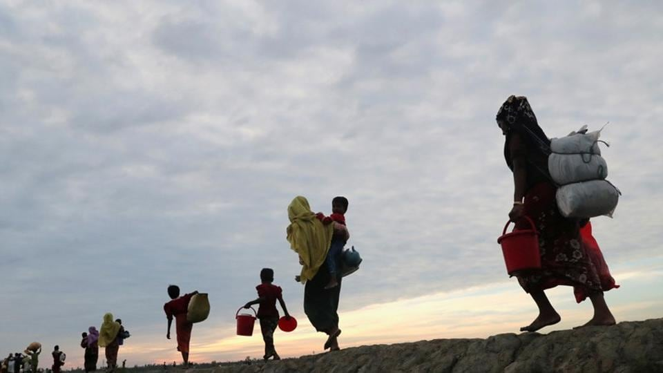 Rohingya refugees walk after crossing the Naf River with an improvised raft to reach to Teknaf in Bangladesh.