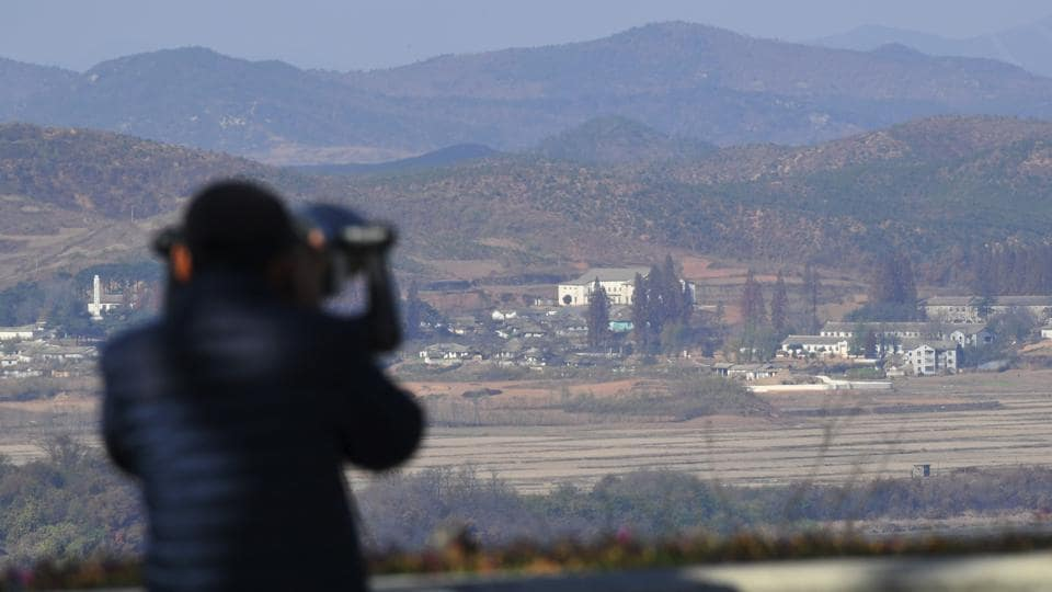 A woman looks through binoculars towards North Korea from a South Korean observation post in Paju near the Demilitarized Zone (DMZ) dividing the two Koreas.