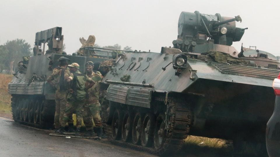 Soldiers stand beside military vehicles just outside Harare, Zimbabwe, on November 14,2017.
