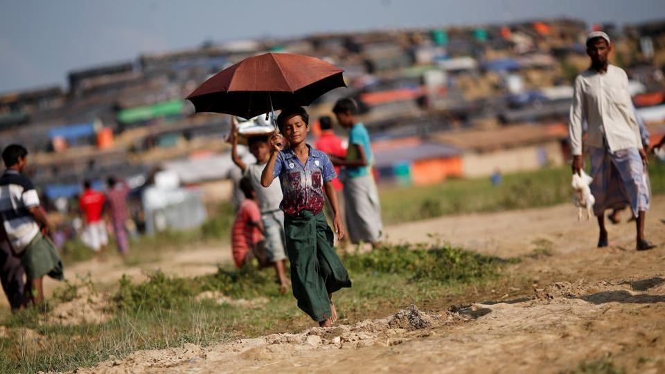 Nur Hafes, 12, a Rohingya refugee, carries an umbrella as shade from the sun at Palong Khali refugee camp, near Cox's Bazar, Bangladesh. Twelve-year-old Nur would rather be in school or playing football with friends back home in Myanmar. His family displaced; Nur is now the sole breadwinner for seven younger siblings and his mother taking refuge in Bangladesh. (Adnan Abidi / REUTERS)