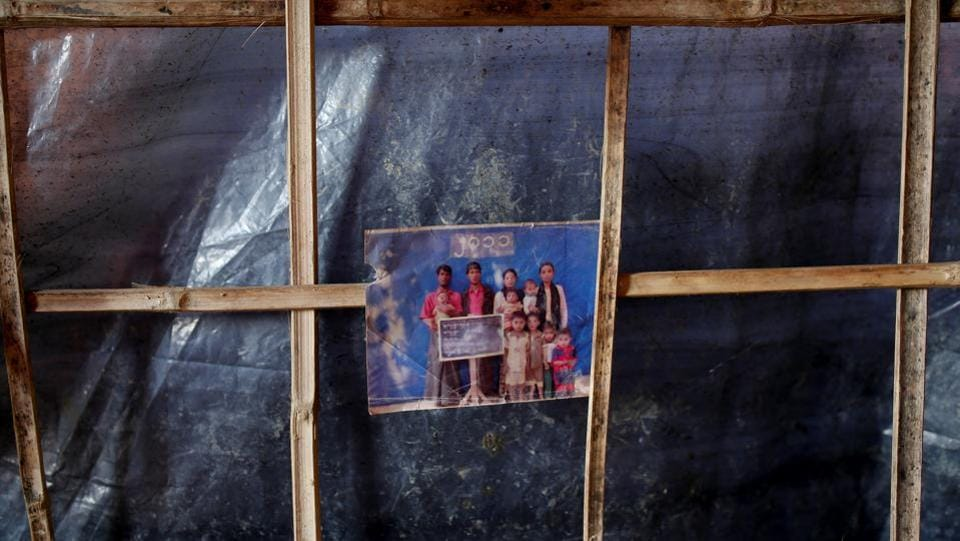 A family photograph hangs in Nur Hafes' shelter at the refugee camp. Gathering a few belongings - a blanket to protect against rain, identity papers and a couple of old photos– Rabia and family fled to Zaw Mat Tat, south of Maungdaw and eventually crossed over to the Bangladesh side of the Naf River. Her husband left them midway and has not been seen since.  (Adnan Abidi / REUTERS)