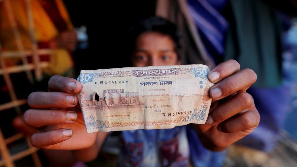"Nur shows a 50 Bangladeshi Taka banknote (Rs 40), which he received as aid from a local Bangladeshi Muslim cleric. ""Sometimes I get 50 or 100 taka and some days I come back empty-handed,"" he said, (Adnan Abidi / REUTERS)"