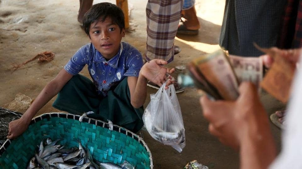 Nur Hafes looks at a vendor as he buys fish at Palong Khali refugee camp. Even while evading the army in Myanmar, Nur was a huge help to his family --reselling produce in their village market that his father had bought wholesale. (Adnan Abidi / REUTERS)