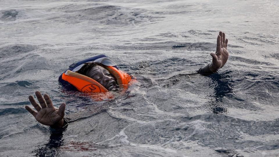 A migrant tries to board a boat of the German NGO Sea-Watch in the Mediterranean Sea on November 6, 2017.