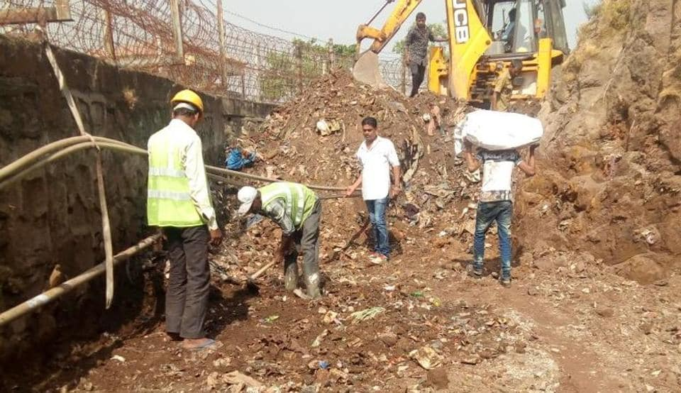 Workers clear the heap of garbage.