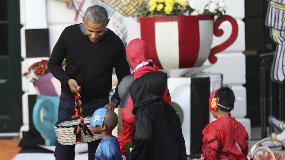 Barack Obama hands treats as he and first lady Michelle Obama welcome children from Washington area and children of military families to trick-or-treat celebrating on Halloween, October 31, 2016.  (AP File Photo)