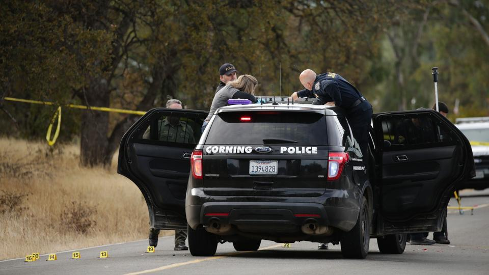 Law enforcement officers and a crime scene photographer examine a police vehicle that was involved in a shooting in the morning on November 14, 2017, in Rancho Tehama.