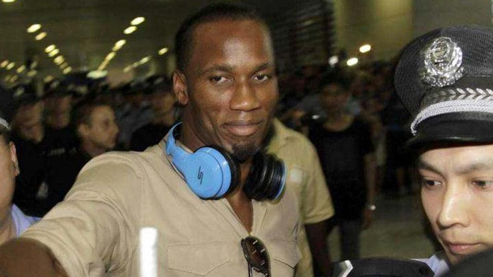 Former Chelsea star Didier Drogba is escorted by police officers upon his arrival at Pudong International Airport in Shanghai in June 2012. Drogba signed with Chinese soccer club Shanghai Shenhua on a two-year contract that reportedly made him China's hig