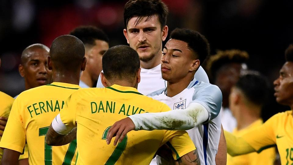 England's Jesse Lingard, Harry Maguire and Brazil's Dani Alves interact after their international friendly encounter.