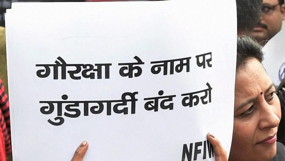 An NGO activist displays a placard during a protest demanding justice for the mob lynching victim Umar Khan , at Bikaner House in New Delhi on Wednesday.
