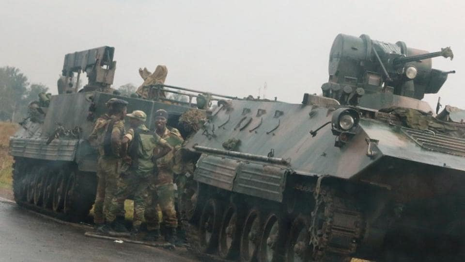 Soldiers stand beside military vehicles just outside Harare, Zimbabwe, on Tuesday.