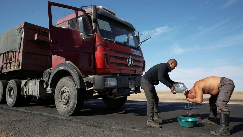A truck driver washes himself with bottled water on the highway for delivering coal to China at Khangobd Soum in the Gobi desert, Mongolia. This serpentine crawl towards the border can take up to a week. (B. Rentsendorj / Reuters)