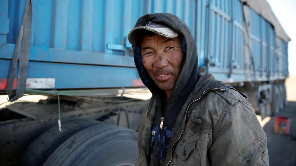 A truck driver repairs his truck on the side of the road near the China-Mongolia border. With Gobi miners hoping to boost output further next year in a bid to take advantage of higher prices in China the bottlenecks are expected to get worse. (B. Rentsendorj / Reuters)