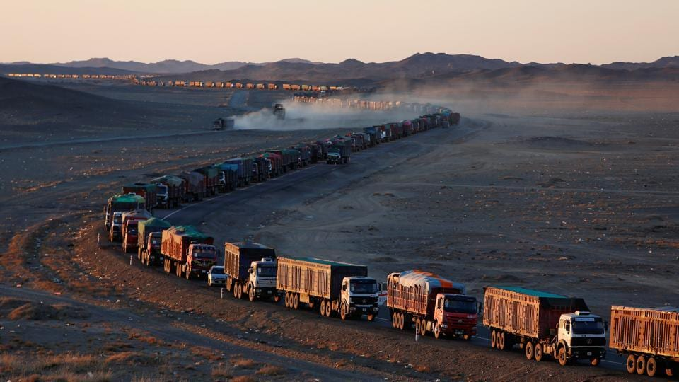 Thousands of heavy-duty trucks loaded with coal line up along the Mongolia-China border in the Gobi desert. A rebound in coal prices and a surge in exports to China this year have meant a bonanza for miners in Mongolia but long delays along the export route threaten this burgeoning lifeline in an ailing economy. (B. Rentsendorj / Reuters)