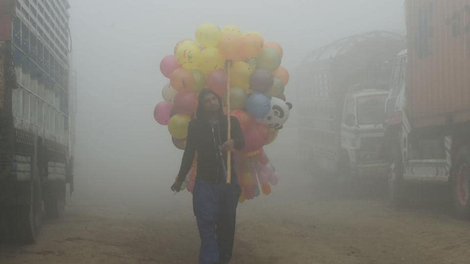 A Pakistani vendor carries balloons on a street amid heavy smog in Lahore. NOAA released satellite pictures and explained the reasons behind such a polluting atmosphere in major parts of north India and Pakistan.