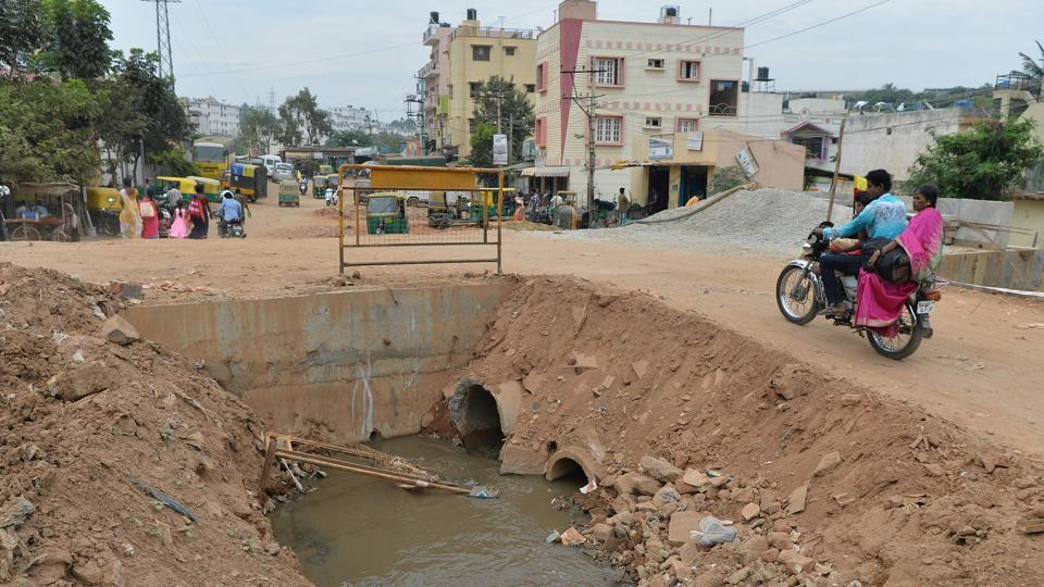 This photograph taken on November 1, 2017 shows a motorist passing an open sewage canal under repair in Bangalore.  (Manjunath Kiran / AFP)