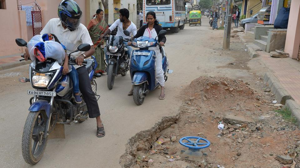 In this photograph taken on November 1, 2017, motorists ride past a pothole created during road repair work in Bangalore. (Manjunath Kiran / AFP)