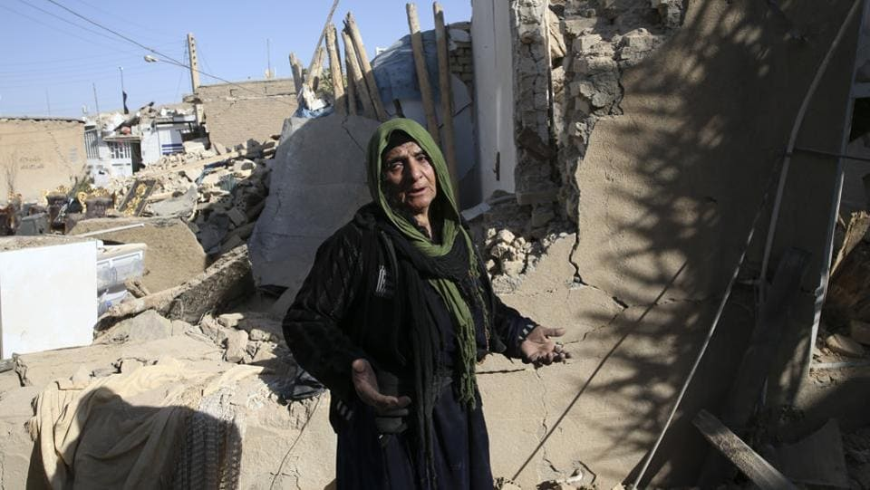 An earthquake survivor speaks at her destroyed house in western Iran. Many working-class survivors lost everything amid severe damage to social housing blocks built under a scheme championed by former president Mahmoud Ahmadinejad. (Vahid Salemi / AP)