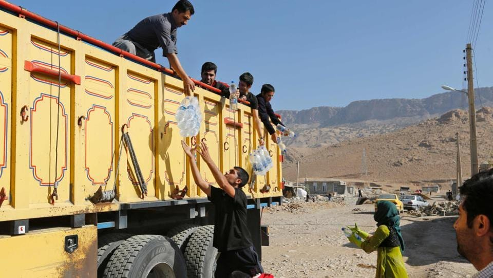 Iranians receive food aid in Kouik village near Sarpol-e Zahab, two days after the 7.3-magnitude quake struck Iran's Kermanshah province. Many volunteers have rushed to help the victims but survivors say not enough is being done. The quake contaminated drinking water supplies and knocked out electricity, phone and gas services. (Atta Kenare / AFP)
