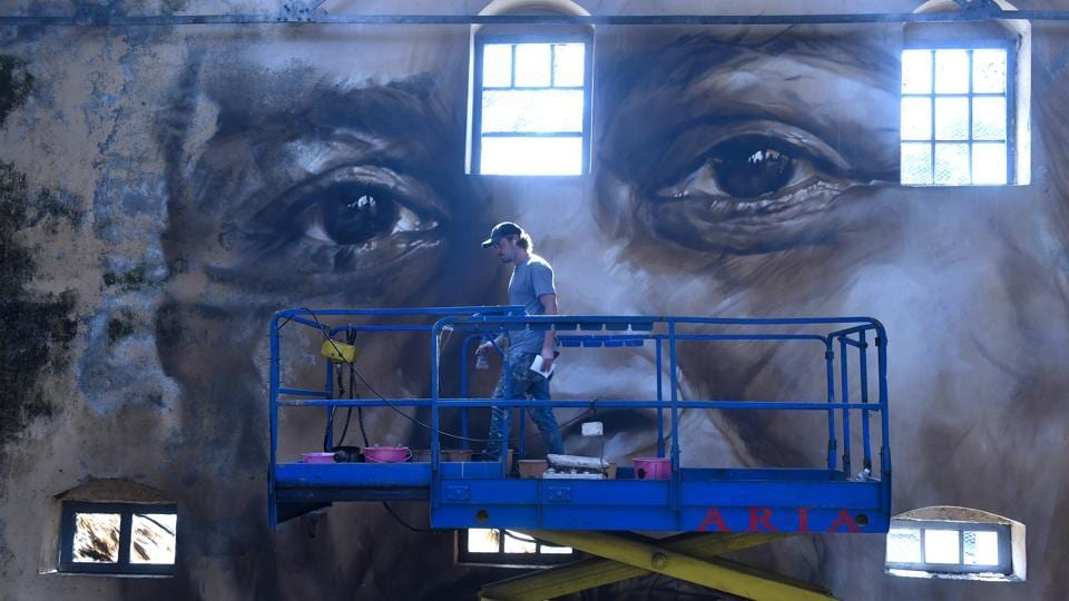 Australian artist Guido Van Helten paints a portrait of a lady as part of the Sassoon Dock Art Project at Sassoon Dock.Thirty artists from around the world have given the bustling 142-year-old Sassoon Docks, home to Mumbai's traditional Koli fishing community, a colourful makeover as part of the St+art Urban Art Festival. (Anshuman Poyrekar / HT Photo)
