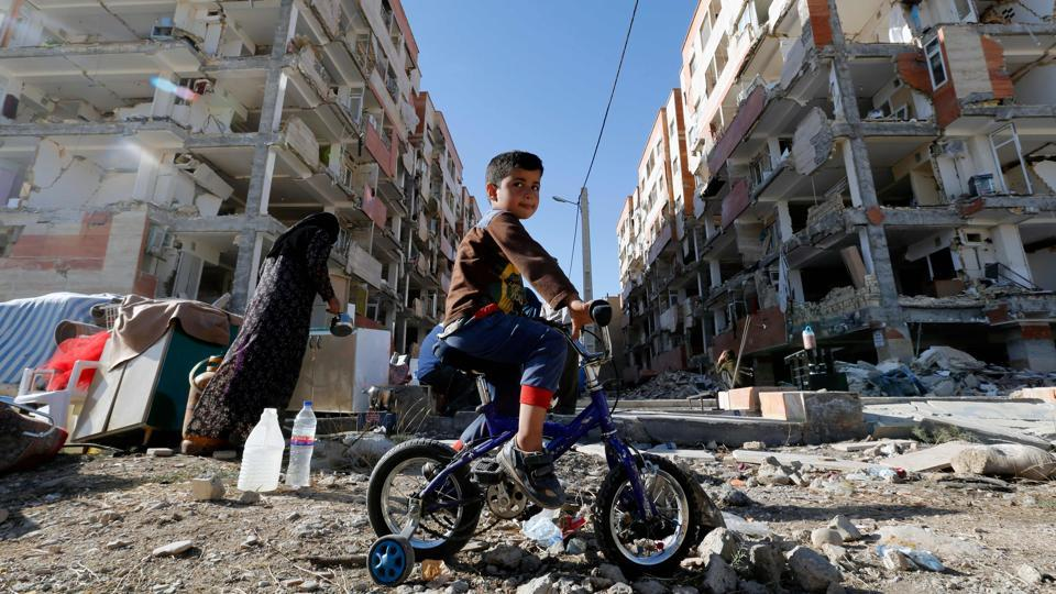 An Iranian boy rides a bicycle through rubbled buildings in  Iran's Kermanshah province near the border with Iraq. Several buildings and houses lay in complete ruins, while others stood partially disfigured. (Atta Kenare / AFP)