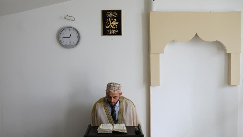 An Imam reads the Quran in a makeshift mosque during Friday prayers. The Islamic community says local authorities have repeatedly ignored requests for new mosques to be built. The shortage raises questions about the country's commitment to minority rights, an important gauge of its readiness for membership of the European Union. (Marko Djurica / REUTERS)