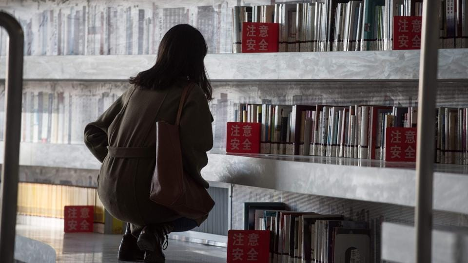 "But readers expecting to pluck tomes from its terraced shelves are in for a surprise. Most books are in other rooms with more classic library bookshelves. ""There's quite a big difference between the photos and reality,"" said Jiang Xue, a 21-year-old medical student left perusing one of the more robustly stocked sections: propaganda about the ruling Communist Party's recent congress. (Fred Dufour / AFP)"