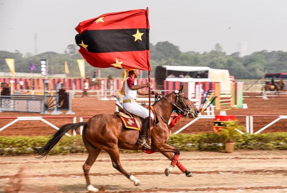 A cadet hoisting the flag while riding a horse to honour the chief guests at the Southern Star Horse Show-2017 at Pune Race Course on Thursday. (Sanket Wankhade/HT PHOTO)