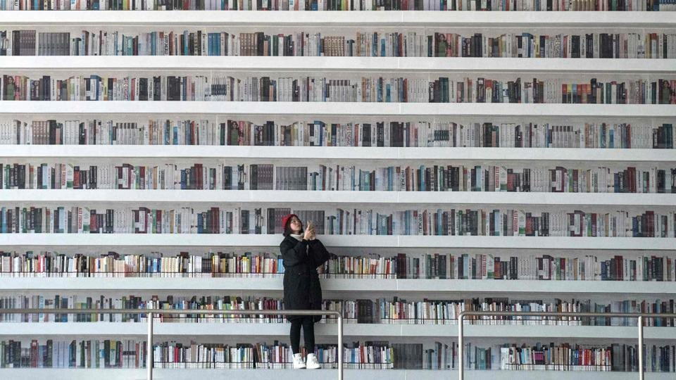 A woman takes a selfie at the Tianjin Binhai Library. This futuristic Chinese library has wowed book lovers around the world with its white, undulating shelves rising from floor to ceiling, but read between the lines and you'll find something is missing. Those rows upon rows of book spines are mostly images printed on aluminium plates that make up the backs of shelves. (Fred Dufour / AFP)