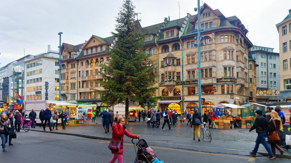 Basel in Switzerland. During Christmas, buildings and bridges are magically lit up and numerous pine trees are decorated on Europe's longest 'Christmas Street'.