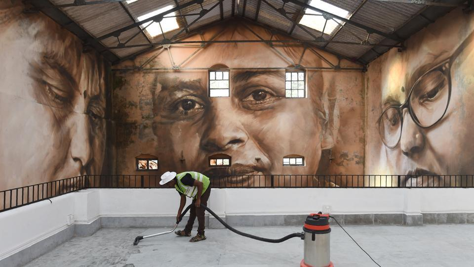 A worker cleans the viewing area in front of a photo mural at Sassoon Dock. Thirty artists from around the world have given the bustling 142-year-old Sassoon Docks, a colourful makeover as part of the 2017 edition of the St+art Urban Art Festival in Mumbai. (Indranil Mukherjee / AFP)
