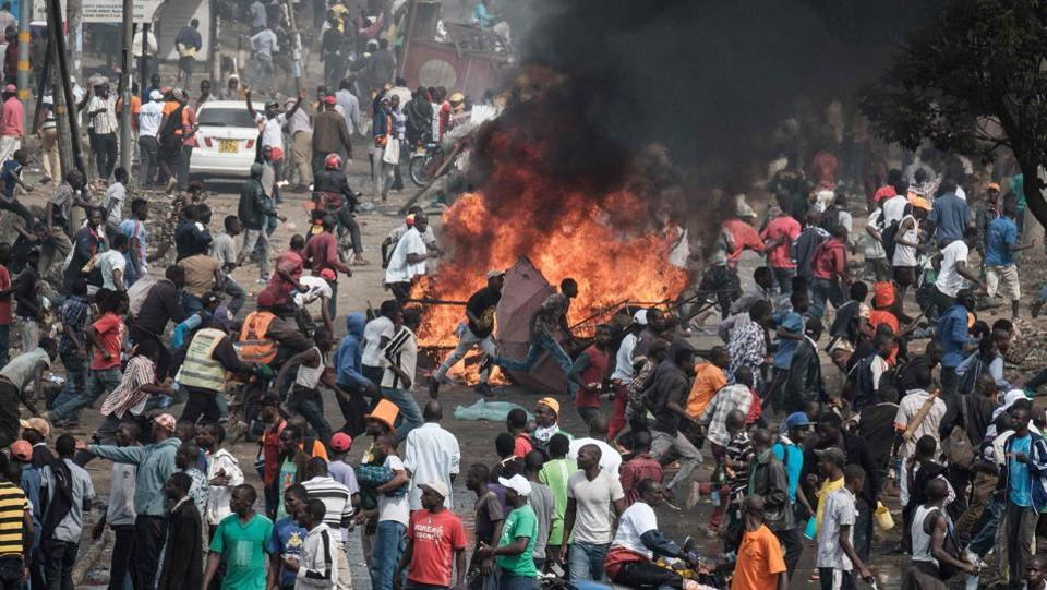 Supporters of Kenyan's opposition party  react following the sound of gunshots during a demonstration  in Nairobi. Supporters had earlier accused police of stopping them at the  main highway from going to the airport to greet Odinga. The confrontations were aired on live television. (Yasuyoshi Chiba / AFP)