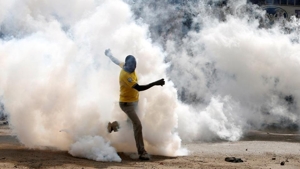 A man makes his way through rising tear gas fired by riot police officers to disperse supporters of Kenyan opposition leader in Nairobi. Police have said five people were killed by mobs that stoned them to death when they were caught stealing during the confrontations. But mortuary attendants and eyewitnesses said police shot them. (Baz Ratner / REUTERS)