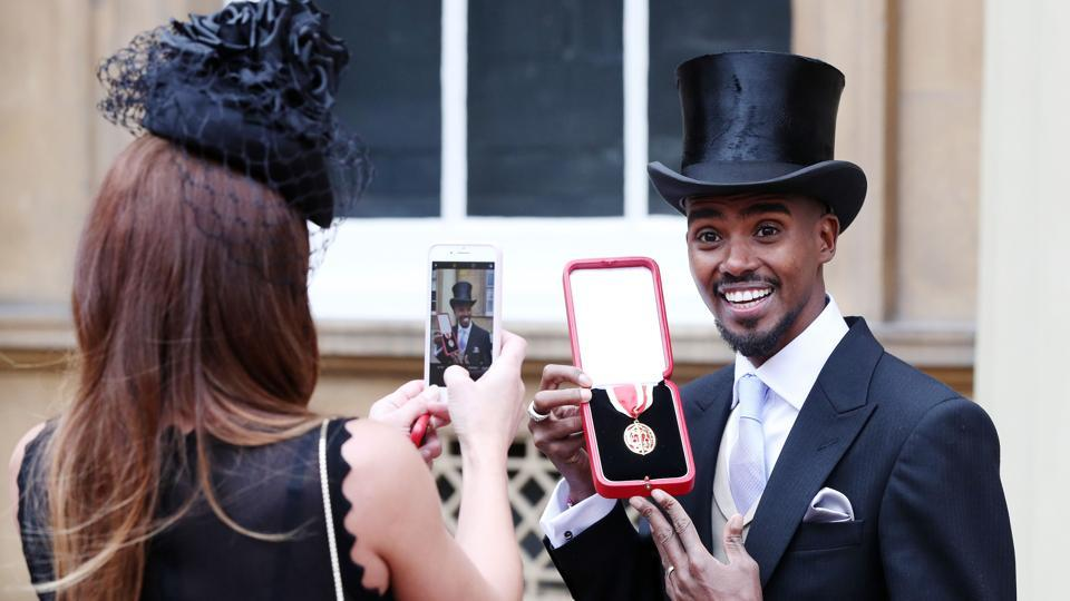 Britain's Mo Farah holds his medal and poses for a photograph for his wife Tania, after being knighted as a Knights Bachelor during an investiture ceremony at Buckingham Palace, in London on November 14, 2017. (Jonathan Brady / PA / AFP)