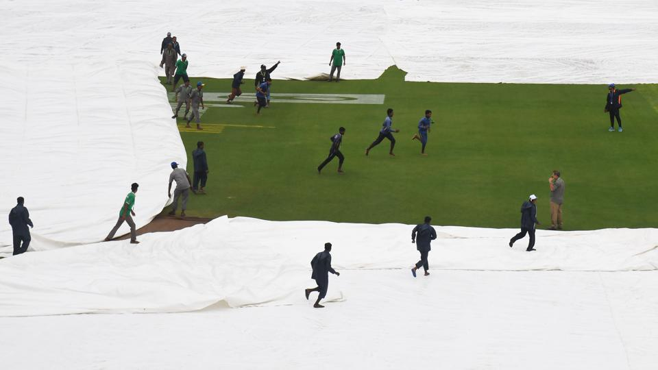 Grounds staff cover the pitch after play was delayed by rain at the start of the first Test between India and Sri Lanka at the Eden Gardens cricket stadium in Kolkata on November 16, 2017. (Dibyangshu Sarkar / AFP)