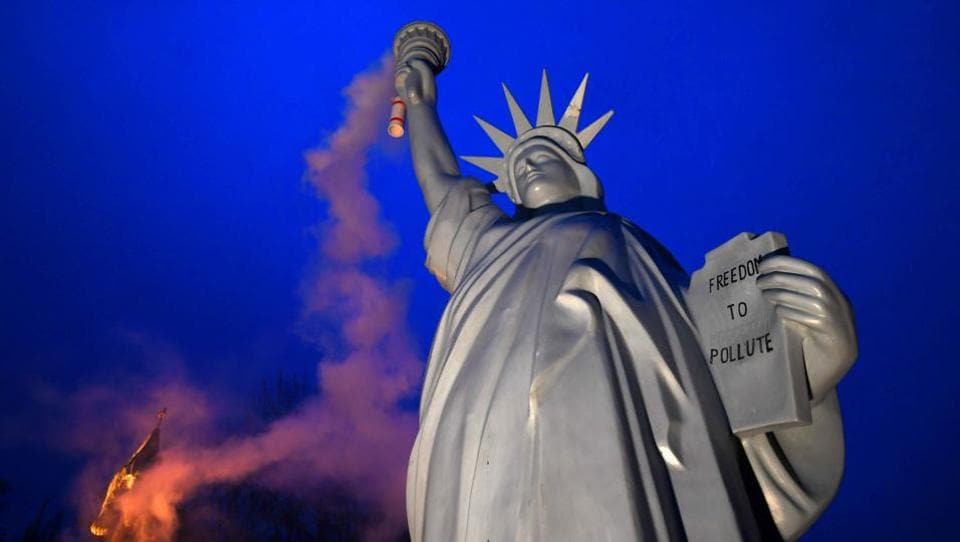 A replica of the Statue of Liberty emits smoke from the torch created by Danish artist Jens Galschiot and displayed at the Rheinaue park during the COP23 United Nations Climate Change Conference in Bonn, Germany on November 16, 2017. (Patrik Stollarz / AFP)