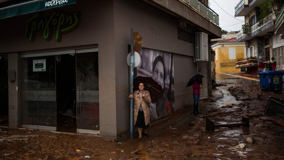 Women holding umbrellas stand next to a damaged shop, in a flooded street of Mandra, northwest of Athens on November 15, 2017. At least seven people died and more were missing after a strong overnight downpour flooded three towns in Greece, officials said. (Angelos Tzortzinis / AFP)