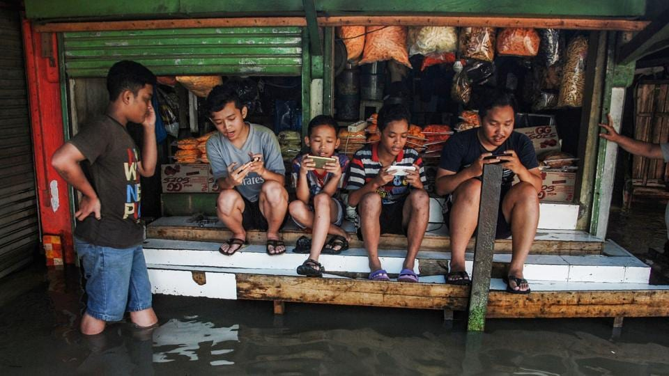 Indonesian youths sit on a table while playing games at a game centre surrounded by floodwaters after seasonal rains hit the area around Bandung, West Java province on November 17, 2017. (Timur Matahari / AFP)