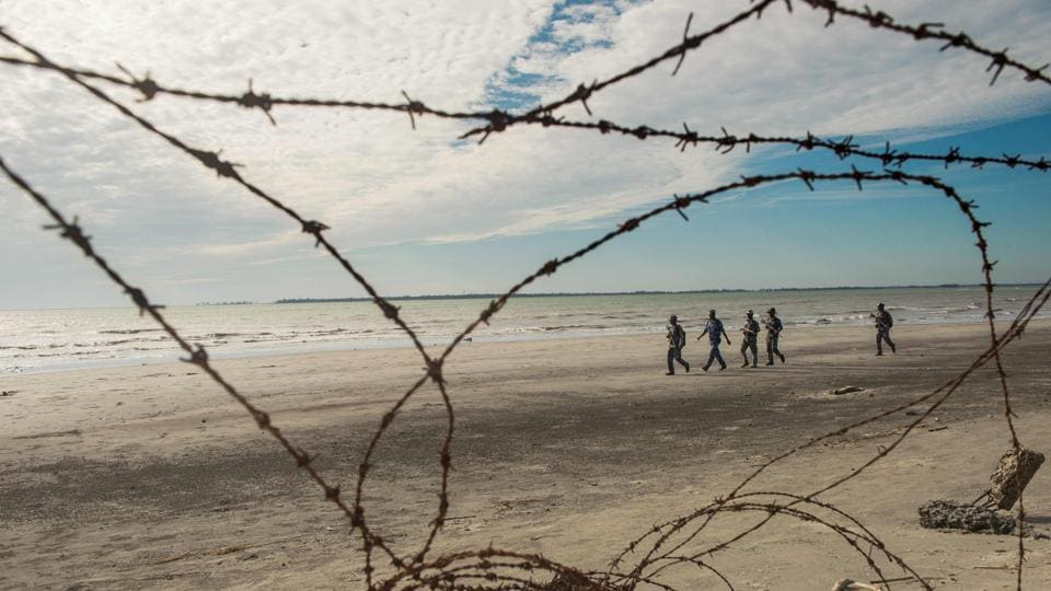 Myanmar border police patrol the beach near a makeshift camp in Rakhine state in Myanmar, where hundreds of Rohingya wait in makeshift camps before crossing over to Bangladesh, on November 12, 2017.  (Phyo Hein Kyaw / AFP)