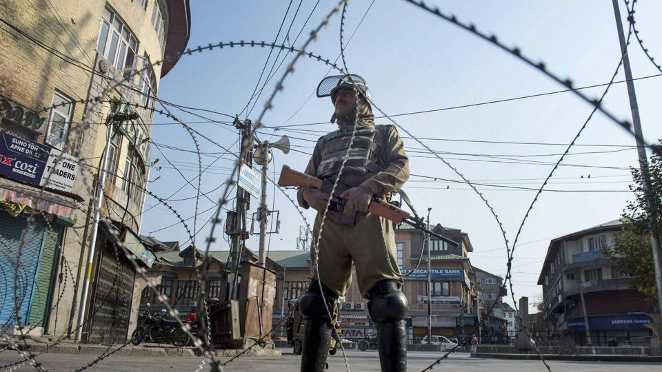 A security jawan stands guard during restrictions and strike in Srinagar.