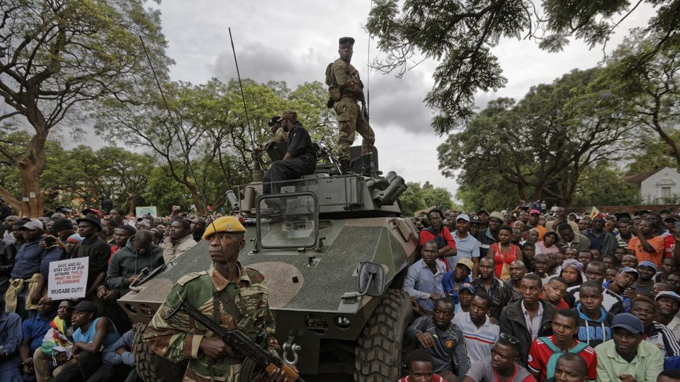 Army soldiers stand guard as protesters demanding President Robert Mugabe exit gather on the road leading to the State House in Harare, Zimbabwe, on Saturday.