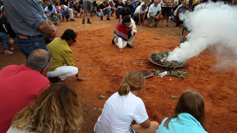 Guests take part in a smoking ceremony with green gum-leaves burning over a small fire during the arrival of Mungo Man and ancestors at the Balranald Aboriginal Cemetery on November 17, 2017 in Balranald. The bones' removal to Canberra for study, roughly 600 km east of Lake Mungo, had angered the indigenous community there. (Lisa Maree Williams / Getty Images)
