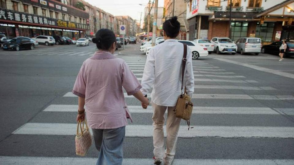 Gay couple Xiaoxiong (right) and Xiaojing walk on a street in Sheynyang, China, in July.