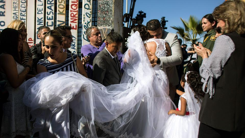 "Bride Evelia Reyes and groom Brian Houston, living on different sides of the US-Mexico border, embrace after getting married during the annual ""Opening the Door of Hope"" event at the border fence gate in Playas de Tijuana, Mexico. It was the sixth time that the gate opened since 2013, allowing people from the US and Mexico who cannot legally cross the border to meet their families without fear of deportation. (Guillermo Arias / AFP)"