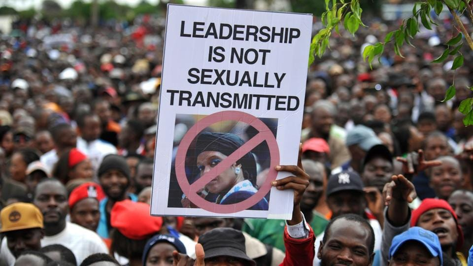 People hold an anti-Grace Mugabe placard during a demonstration demanding Mugabe's resignation on November 18, 2017 in Harare. In a draft impeachment motion, ZANU-PF said Mugabe had abused his constitutional mandate to favour his wife Grace, 52, whose tilt at power triggered the backlash from the army. (Zinyange Auntony / AFP)