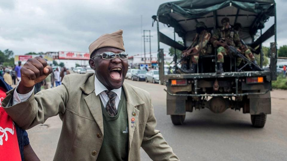 "A man cheers as a military vehicle loaded with soldiers drives past him during a rally to demand the resignation of Robert Mugabe at the a public ground on November 18, 2017, in Harare. Since last week, Mugabe has been confined to his lavish ""Blue Roof"" residence in Harare, apart from two trips to State House to meet generals and one to a university graduation ceremony. (AFP Photo)"